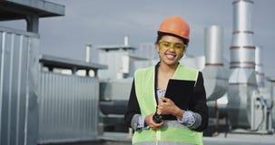 Przed kamera portretem Afrykański charyzmatyczny dama inżynier na dachu budowa w hełmie zbiory wideo