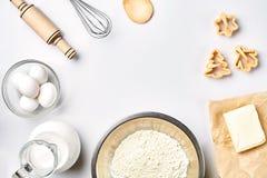 Przedmioty i składniki dla piec, klingeryt foremki dla ciastek na białym tle Mąka, jajka, toczna szpilka, śmignięcie zdjęcia stock
