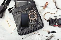 Przedmioty na drewnianym tle: rzemienna torba, kamera, smartphone Fotografia Royalty Free