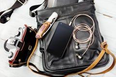 Przedmioty na drewnianym tle: rzemienna torba, kamera, smartphone Zdjęcie Stock