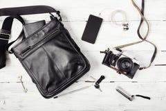 Przedmioty na drewnianym tle: rzemienna torba, kamera, smartphone, klucze, latarka Strój miastowy podróżnik Obrazy Stock