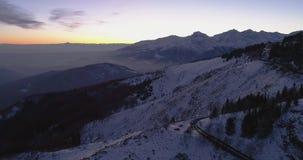 Przedni powietrzny odgórny widok nad samochodem z reflektorami podróżuje na zimy śnieżnej halnej drodze Błękitny godzina świt lub zbiory