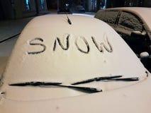 Przednia szyba samochód osobowy zakrywający z śniegiem, na którym słowo zdjęcia royalty free