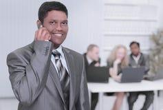 Przedpole biznesmen opowiada na telefonie komórkowym w biurze fotografia royalty free
