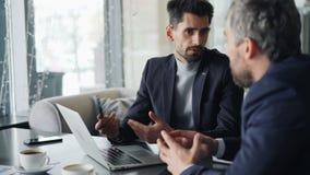 Przedsiębiorców mężczyźni komunikuje w kawiarni dyskutuje ewentualnego partnerstwo zbiory