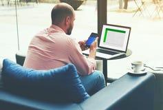 Przedsiębiorca analizuje pieniężną informację jako grafika i mapy na jego smartphone i notatniku Fotografia Royalty Free