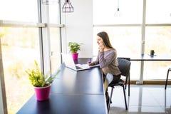 Przedsiębiorca dzwoni na telefonie i działaniu na linii z laptopu obsiadaniem w biurku przy biurem Zdjęcia Stock
