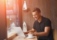 Przedsiębiorca ono uśmiecha się podczas gdy pracujący przy laptopem w pogodnej kawiarni zdjęcia royalty free