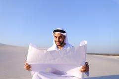Przedsiębiorczy męski sheikh biznesmena obsiadanie z białym papierem wewnątrz Zdjęcie Stock