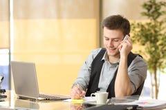 Przedsiębiorca pracuje na telefonie przy biurem Fotografia Royalty Free