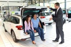 Przedstawicielstwo firmy samochodowej rada - sprzedawcy i klienci gdy kupujący samochód obraz royalty free