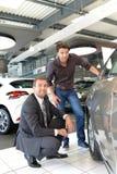 Przedstawicielstwo firmy samochodowej rada - sprzedawcy i klienci gdy kupujący samochód obrazy royalty free