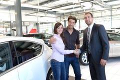 Przedstawicielstwo firmy samochodowej rada - sprzedawcy i klienci gdy kupujący samochód zdjęcie royalty free