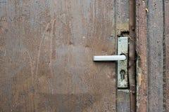 Przegi?ty doorknob w starym o?niedzia?ym drzwi obraz stock