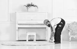Przegięty pracownik stacza się dywan Mężczyzna usuwa białego dywanika od pokoju z tatuażem na ręce Domowy odświeżania pojęcie fotografia royalty free