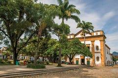 Przegląd stary barwiony kościół, ogród z drzewami i brukowiec ulica w Paraty, zdjęcia stock