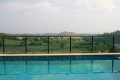 Przegląda błękitnego pływackiego basenu plenerowego kurort na niebieskim niebie i zielenieje mou Zdjęcie Stock