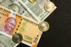 Przegląda Indiańskie waluty, 200, 500 i jeden rupie notatek, z monetami na czarnym tle zdjęcie stock