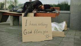 Przegrany młody bezdomny mężczyzna sen na ławce przy miasto ulicą zdjęcie royalty free