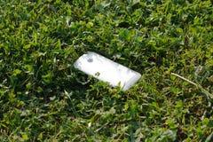 Przegrany smartphone lying on the beach w trawie Fotografia Royalty Free