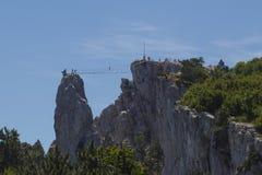 Przejście turyści na zawieszenie linowym moście między górami zdjęcia royalty free