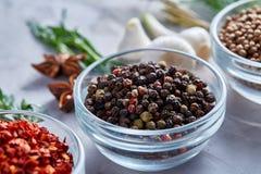 Przejrzyści szklani puchary z peppercorns i suszący chłodny wśród egzotycznych spicies, zakończenie, odgórny widok, selekcyjna os obraz stock