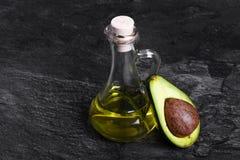 Przejrzysta butelka organicznie avocado olej i rżnięta avocado owoc na zmroku - szary tło pojęcia zdrowe jedzenie Obrazy Royalty Free