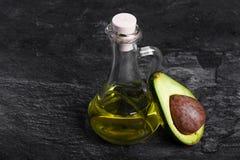 Przejrzysta butelka organicznie avocado olej i rżnięta avocado owoc na zmroku - szary tło pojęcia zdrowe jedzenie Fotografia Stock