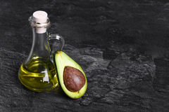 Przejrzysta butelka organicznie avocado olej i rżnięta avocado owoc na zmroku - szary tło pojęcia zdrowe jedzenie Fotografia Royalty Free