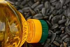 Przejrzysta butelka z słonecznikowym olejem na stosie słonecznikowi ziarna Zdjęcia Stock
