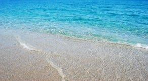 Przejrzysta głęboka błękit fala morze który łama na brzeg w Zdjęcie Royalty Free