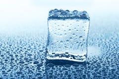 Przejrzysta kostka lodu z odbiciem na błękitnym szkle z wodnymi kroplami Obrazy Royalty Free