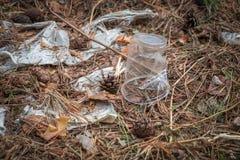 Przejrzysta plastikowa filiżanka i poszarpana torba w lasowym problemu ekologia obrazy royalty free