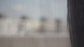 Przejrzysta szara zasłona na okno w ranku, delikatnie dotykającym wiatrem Widok od okno na mieście zbiory