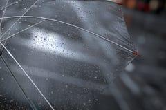Przejrzysty parasol z dżdżystymi kroplami zamkniętymi up na ulicznym mieście zaświeca tło royalty ilustracja