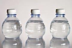 Przejrzysty szklany pełny woda blisko butelki woda mineralna Obraz Royalty Free