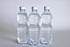 Przejrzysty szklany pełny woda blisko butelki woda mineralna Zdjęcie Royalty Free