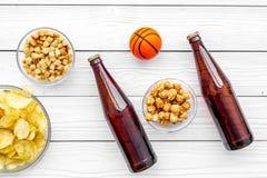 Przekąski dla oglądać sport gry na TV i dopasowania Chipsy, popkorn, rusks blisko piją i piłka na białym drewnianym tle obraz stock