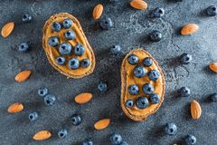Przekąski z chlebem, masłem orzechowym i czarnymi jagodami, pojęcia zdrowe jedzenie Mieszkanie nieatutowy, odgórny widok Obrazy Royalty Free