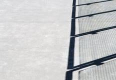 Przekątna cienie na cementowym przejściu od metalu i szklanej panel bariery fotografia stock