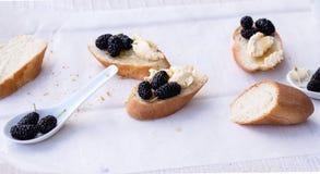 Przekąsza na francuskim baguette na drewnianej desce Zdjęcie Stock