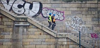 Przekazuje i hełmy Bremen Niemcy, Marzec - 8th, 2017, Dwa pracowników budowlanych chodzi w dół set schodki w przodzie o z viz - Zdjęcie Royalty Free