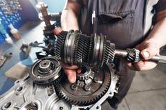 Przekrój poprzeczny samochodowy gearbox mechanik praca w garażu ręka mechanik w pracujących ubraniach Fotografia Royalty Free