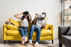 przelękła amerykanin afrykańskiego pochodzenia para w rzeczywistość wirtualna słuchawek siedzieć obraz stock