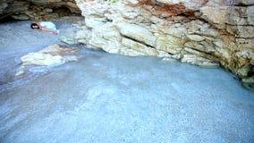 Przelękła dziewczyna kłama na piasku w kamiennej grocie zbiory