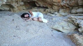 Przelękła dziewczyna kłama na piasku w kamiennej grocie i przypływ morze zbliża się ona zdjęcie wideo