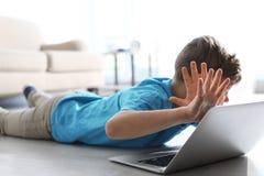 Przelękły małe dziecko z laptopem na podłodze Niebezpiecze?stwo internet obrazy stock