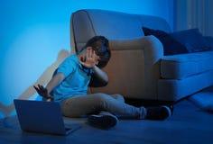 Przelękły małe dziecko z laptopem na podłodze w ciemnym pokoju obrazy royalty free