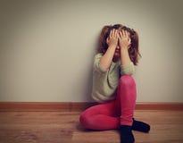 Przelękły płaczu dzieciaka dziewczyny obsiadanie na podłoga z zamkniętą twarzą fotografia stock