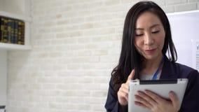 Przemyślana, azjatycka bizneswoman używająca tabletu w biurze zbiory wideo